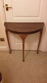 Semi circurcular mahogany table with carved queen ann legs and fluted edge