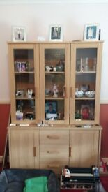 beautiful light pine coloured living room unit.glass shelves on top which light up and storage space
