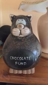 Ceramic brown cat money box with chocolate fund on the front