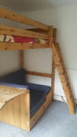Wooden single bunk bed with desk beneath and seat that converts to 2nd bed .