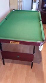 6ft snooker/pool table, includes both sets of balls, cue, rest etc. Folds away for easy storage.