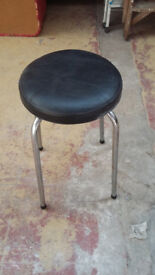 round metal framed stool with black leather look padded seat