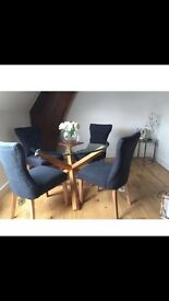 Wood and glass round dining table and dark grey button chairs