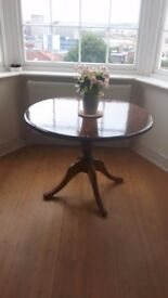 Round dining table, solid wood, with dark stain & gloss finish
