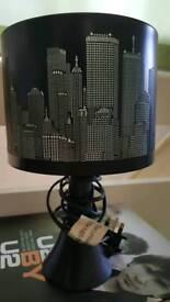 Table lamp with black skyline shade.