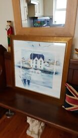 large gold framed picture of a boathouse