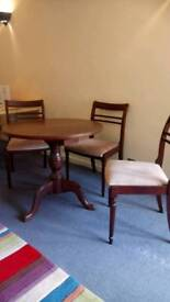A round table with three chairs