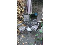 Glass top garden table with four folding chairs