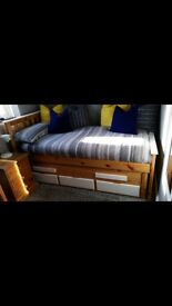 Solid Pine truckle bed with one mattress for sale.
