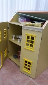 Childrens dolls house with lots of different furniture