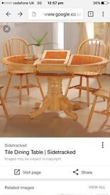 Solid dining table with orange tiled top and chairs