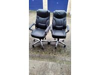Two large comfortable heavy duty leather office chairs.
