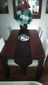 Dark wood dining table and 4 cream faux leather chairs