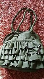 Green bag with ruffle front.