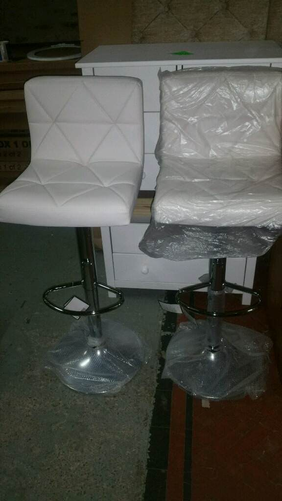 A brand new pair of white breakfast bar stools.
