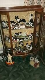 Selection of collie dog ornaments in a glass cabinet