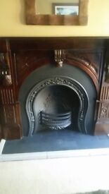 Cast iron fireplace with ornate dark brown wood surround.