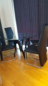 Modern dining set, round glass top with 4 black leather look chairs good condition