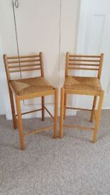 Pair of wooden stools with raffia seats in good condition