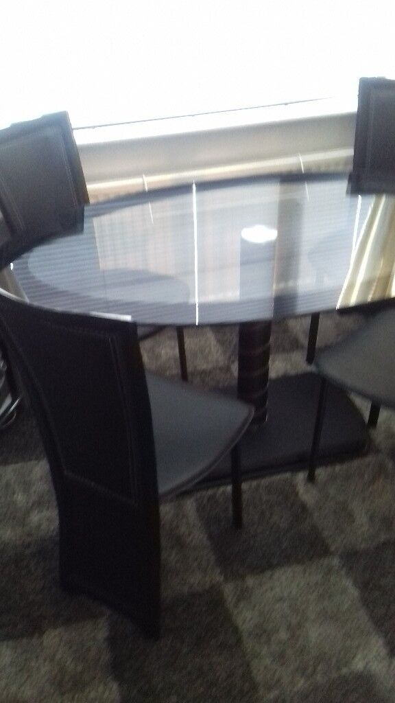 Black glass oval dining table and 4 black faux leather chairs