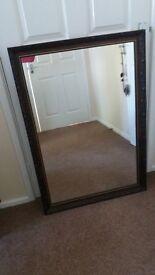 Dark brown wooden mirror.