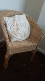 wicker half round chair and nice flower cushion