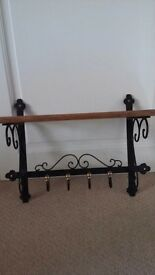 Ornate iron and wood wall hanging coat rack, with wooden hat shelf