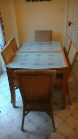 glass topped extendable table with 6 wicker chairs