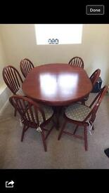 Round extendible dining table with six chairs