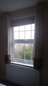 Selection of curtains in neutral colours for windows and doors including hanging rails