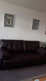 Large two seater dark brown bonded leather sofa.very good condition.under a year old