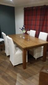 Pine dining table and 4 chairs. Chair covers machine washable.great condition
