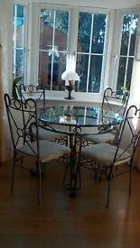 Glass and metal round dining table and 4 chairs with ivory upholstery