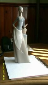 Porcelain figure of a Lady By Lladro of Spain . Size 12 inch in length