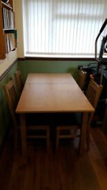 Oak table and 4 chairs with middle extension. Chairs have ladder backs with brown faux leather seats