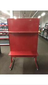 Red metal peg board with 4 shelves