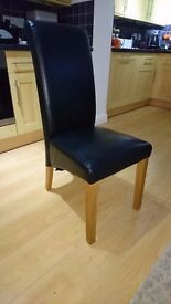 4 Black leather effect dining chairs.