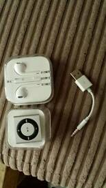 Ipod shuffle 2gb, earphones and blue tooth speaker.