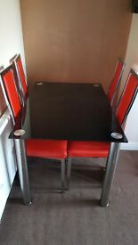 Black Glass Dining Room Table with Red Chairs