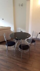 Black Glass table and four chrome chairs - used