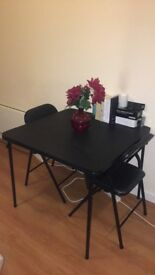 FANTASTIC BLACK DINING TABLE PLUS FOUR FOLDABLE CHAIRS WITH LEATHER SEAT PADS - GREAT FOR ANY SPACE