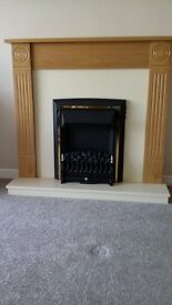 Freestanding light oak fireplace with integrated electric coal effect fire .