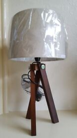 Brand new dark wooden tripod stand with dark cream lamp shade. Energy saving light bulbs can be used