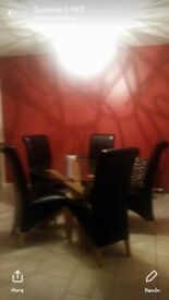 Round glass and oak table and brown leather chairs
