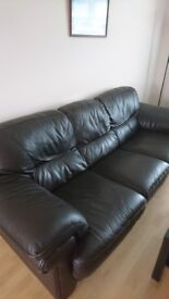 Brown leather three person sofa.
