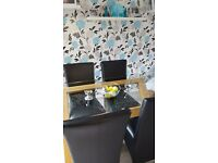 Glass dinning table with 4 black leater chairs
