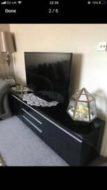 Black glossy ikea tv cabinet and gold rug