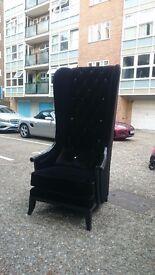 A very tall high-back black studded arm-chair