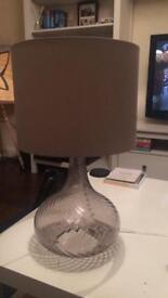 Table lamp with glass base and light grey shade