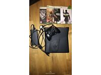 Xbox 360 slim (black) with 4 games.